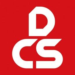 Logo van DCS. DCS staat in witte letters op een rode achtergrond