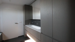 foto van moderne badkamer met op maat gemaakte kasten in hout met een donkere finish en een donkere tegelvloer