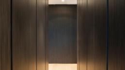 foto van een op maat gemaakte dressing room met kasten in donker hout, een lichte vloer en in het plafond verwerkte spots als verlichting