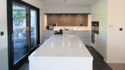 foto van een moderne keuken, wit keukeneiland in het midden met een marmeren werkblad. Achteraan de keuken nog extra werkruimte op op maat gemaakte kasten en langst de zijkant een schuifdeur richting terras