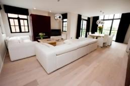 moderne living met witte lederen zetels, houten salontafel, en rechts eettafel met 6 stoelen, donkere gordijnen
