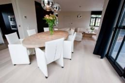 foto moderne, ovale eettafel met 6 stoelen. vaas met bloemen op de tafel, in de achtergrond salon met witte lederen zetels en donkere gordijnen