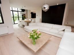foto van moderne living met witte, lederen zetel, houten salontafel, in de achtergrond tafel met 6 stoelen, doorkijk naar keuken, en biljart, donkere gordijnen