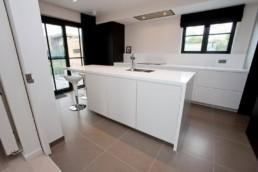 foto van moderne witte keuken met grote, grijze, keramische tegels en zwarte accentmuren