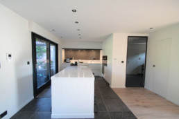Foto van moderne keuken, met keuken eiland, ingebouwde apparaten en grijze tegels tegen muur achter fornuis en keramisch keukenblad