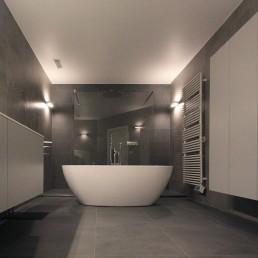 totaalzicht van de badkamer genomen vanaf het afscheidingsmuurtje waarachter het toilet zich bevindt. Zicht op vrijstaand bad, lavabo, wandkast, en inloopdouche achter het vrijstaande bad. Moderne centrale verwarming tegen de rechtermuur met de wandkast