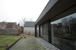 foto van een moderne aanbouw verzorgd door DCS. De aanbouw is bekleed met grote, zwarte Eternit Pictura panelen. Foto van de achterzijde van het huis. De achterzijde van het huis bestaat uit 1 grote, glazen schuifdeur.
