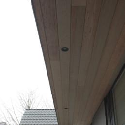foto van een moderne aanbouw verzorgd door DCS. De aanbouw is bekleed met grote, zwarte Eternit Pictura panelen. Foto van overhangend deel, dat als een soort afdak functioneert. Dit werd afgewerkt met hout als plafond, waarin spots werden verwerkt.