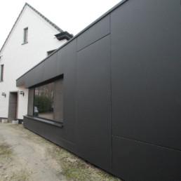 foto van een moderne aanbouw verzorgd door DCS. De aanbouw is bekleed met grote, zwarte Eternit Pictura panelen. Foto werd genomen vanaf de achterzijde van het huis naar de straatkant toe om het lijnenspel van de panelen te tonen.