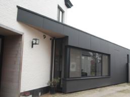 foto van een moderne aanbouw verzorgd door DCS. De aanbouw is bekleed met grote, zwarte Eternit Pictura panelen, genomen uit een andere hoek en dichterbij
