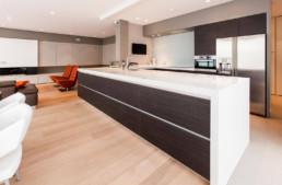 foto van een moderne open living, keuken en eetkamer, detail van de keukenkast gezien vanuit de living