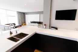 foto van een moderne open living, keuken en eetkamer, foto getrokken vanuit de keuken, met zicht op de living