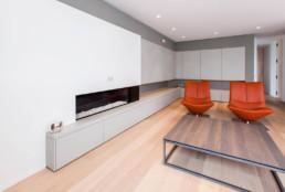 Detail foto van de living. 2 Oranje fauteuils, openhaard ingewerkt in de muur en een op maat gemaakte wandkast