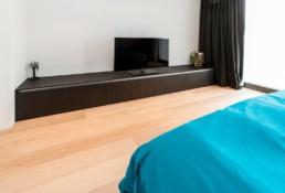 foto van de slaapkamer met een op maat gemaakt tv-meubel, over de gehele breedte dat vlak tegen de grond staat