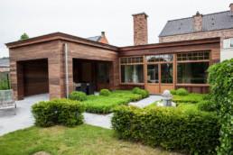 aanbouw langst de buitenkant afgewerkt in hout. foto van het overdekte terras, en de gehele aanbouw met daarvoor een aangelegde tuin