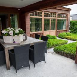 aanbouw langst de buitenkant afgewerkt in hout. foto van het overdekte terras, met in de achtergrond de tuin en dubbele deuren die toegang tot het huis verlenen