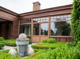 aanbouw langst de buitenkant afgewerkt in hout met grote ramen en een dubbele deur