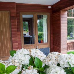 aanbouw langst de buitenkant afgewerkt in hout. foto van het overdekte terras, deuren afgewerkt in hout, 1 deur is een dubbele deur met glas, de andere deur is volledig in hout