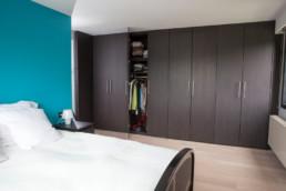 foto van moderne, in donker hout, op maat gemaakte kasten in een slaapkamer. Achter twee deuren zit de doorgang naar de inloopdressing verborgen.