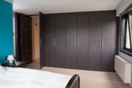 foto van moderne, in donker hout, op maat gemaakte kasten in een slaapkamer. Twee deuren van de kast staan open en onthullen de doorgang naar de inloopdressing.