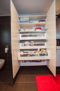 foto van op maat gemaakte, witte 2-deurs kast in badkamer die open staat om te tonen dat er zowel schabben als laden zijn voorzien in de kast