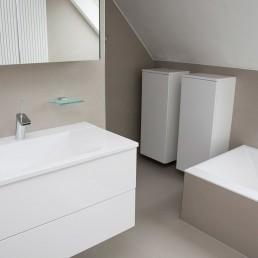 foto van een moderne badkamer onder de schuine kant van het dak. Ligbad, lavabo en kastjes. Op de vloer en tegen de muren werden keramische tegels gebruikt. Boven de lavabo, waaronder er twee schuiven in een hangkast hangen, hangt een spiegelkast.