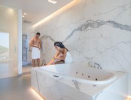 foto van koppel in een moderne badkamer met keramische tegels die de indruk van marmer geven.