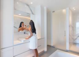 foto van dame die zich aan het opmaken is in een moderne badkamer met keramische tegels die de indruk van marmer geven.