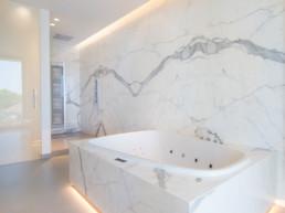 foto van bad en douche in moderne badkamer met keramische tegels die de indruk van marmer geven