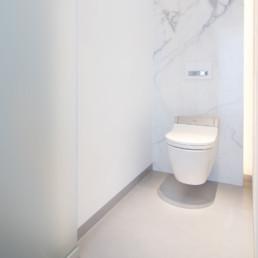 foto van hangtoilet in moderne badkamer met keramische tegels die de indruk van marmer geven