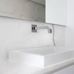 Detailfoto van lavabo in moderne badkamer met keramische tegels die de indruk van marmer geven