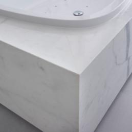 Detailfoto van bad in moderne badkamer met keramische tegels die de indruk van marmer geven
