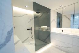 foto van moderne badkamer, foto van de hoek met douche en een deel van de wastafel met daarboven spiegelkasten. op de muur en grond werden keramische grootformaat tegels gebruikt met een marmer effect
