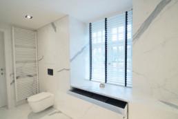 foto van moderne badkamer, foto van de hoek met het hangtoilet. op de muur en grond werden keramische grootformaat tegels gebruikt met een marmer effect