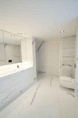 foto van witte moderne badkamer met tegels op de vloer en tegen de muur, ook de kasten werden met dit materiaal afgewerkt. Het gebruikte materiaal heeft een marmer-effect
