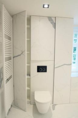 foto van moderne badkamer, foto van de muur met het hangtoilet. rondom het toilet zijn ingebouwde kasten in de muur achter het toilet. op de muur en grond werden keramische grootformaat tegels gebruikt met een marmer effect