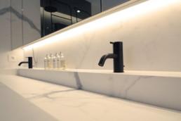 detail foto van de kranen van de wastafel. deze zijn mat-zwart. de wastafel werd ook uitgewerkt in hetzelfde materiaal als de muren en vloer.