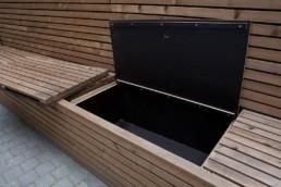 Detail van de bank met opbergvakken waarin tuinkussens of ander tuinmateriaal kan weggeborgen worden, afgeschermd van regen, sneeuw en zon