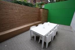 Opbergruimte in de tuin. Muur bekleed met houten latten. Bank waarin opbergruimte is verwerkt en een kast.