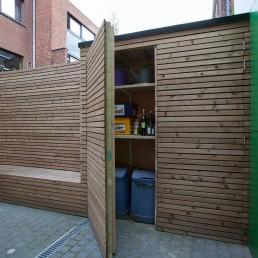 Opbergruimte in de tuin. Muur bekleed met houten latten. Bank waarin opbergruimte is verwerk en een kast waarin vuilbakken en tuingrief kan opgeborgen worden.