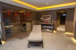 foto van ligbed en handoekenrek met op de achtergrond Sauna ruimte.