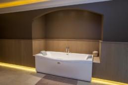 foto van bad in Wellness-ruimte. bruin geverfde muren, houten lambrisering en op de vloer beige, keramische tegels
