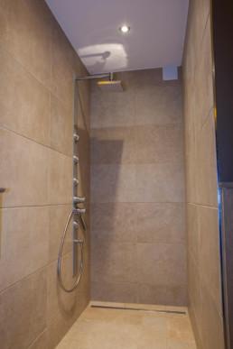 foto van douche in Wellness ruimte. de douche heeft een regendouchekop, de afvoer is in de vloer van de douche ingewerkt. Als verlichting zijn er spots in het plafond verwerkt. in de muur is een verluchting/afzuigsysteem voorzien voor de vochtige lucht