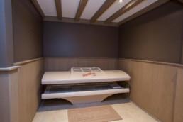 foto van ruimte met zonnebank in het plafond dat verder wit is, zijn balken zichtbaar, de muren zijn bruin geschilderd en onderaan een houten lambrisering