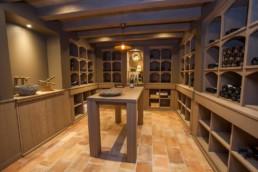 overzichtsfoto van wijnkelder centraal in de ruimte staat een houten tafel met galzen en een fles. Rondom de gehele ruimte zijn schabben voor flessen voorzien, met uitzondering van een deel van de linker muur waar een gootsteen is voorzien
