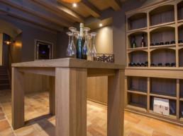 foto van tafel in wijnkelder met daarop fles en glazen
