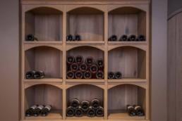 detail foto van flessen op schabben in wijnkelder