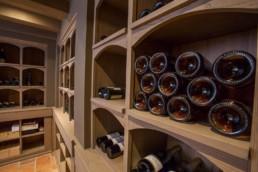 Detail foto van flessen op schabben in de wijnkelder