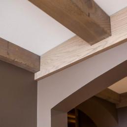 Detailfoto van het plafond. Plafond met houten steunbalken die doorheen de hele ruimte lopen.