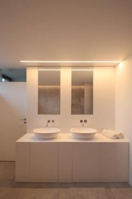 moderne badkamer met beige keramische tegels op de vloer. Witte muren. Zicht op muur met het lavabomeubel dat bestaat uit een kast met deuren. De lavabo's op de kast zijn vrijstaand. boven de lavabo's hangen spiegels